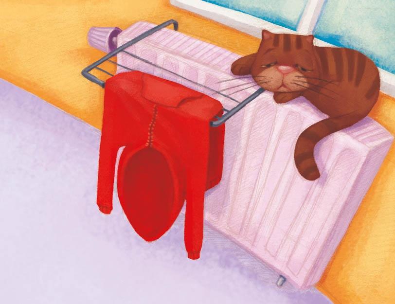 Kot leży na kaloryferze, na którym suszą się ubrania